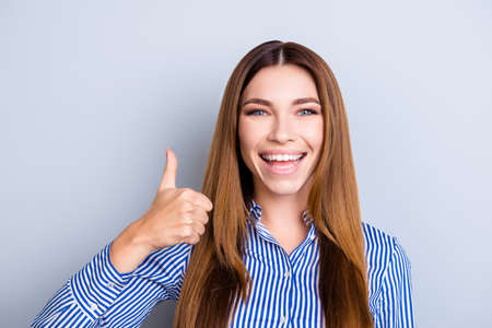 Young confident cheerful lady is very excited and showing thumb up sign, wearing smart shirt, standing on pure blue background Stok Fotoğraf - 87296561