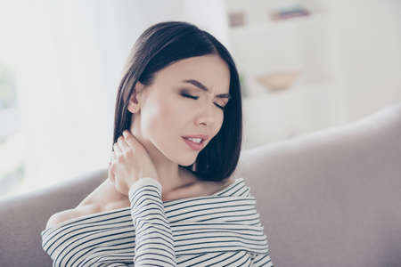 Close up of young frustrated asian lady, having a strong pain in neck. She is at home and alone, sitting on sofa in casual striped outfit