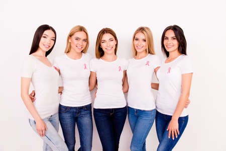 Women healthcare, breast cancer, medicine concept. Portrait of five young girlfriends in white tshirts with pink breast cancer awareness ribbon on chest, isolated on white background, smiling, bonding