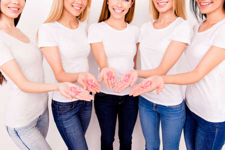 Cropped shot of five girl`s arms holding pink ribbon for day breast cancer awareness, symbolic victory of women living with breast cancer, fighting it, enjoying life, ladies with beaming smiles happy
