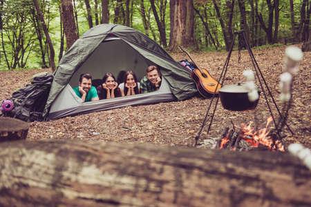 야생 나무에서 캠프장에서 텐트에 누워 두 사랑스러운 커플의 집중된보기, 그래서 행복, 웃 고, 편안 하 고 즐기기, 저녁 식사는 화분에 냄비에 요리입