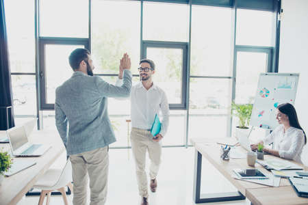 Team work concept. Two friendly handsome brunet guys colleagues, dressed elegant and stunning, are giving high five while passing each other in office, secretary is smiling