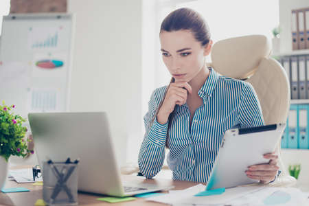 pedant: Serious ponder young business lady economist is thinking which decision to make at her modern light work place in office, wearing strict outfit Stock Photo