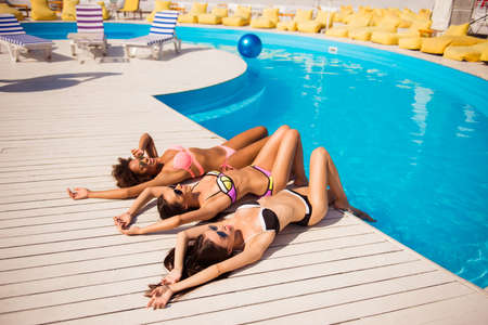 Happy three girls sun bathing near the pool. Attractive skinny girlfriends lie on white wooden floor on their backs, posing flirty in colorful swimming suits. They are so hot and tempting, elegant Banco de Imagens