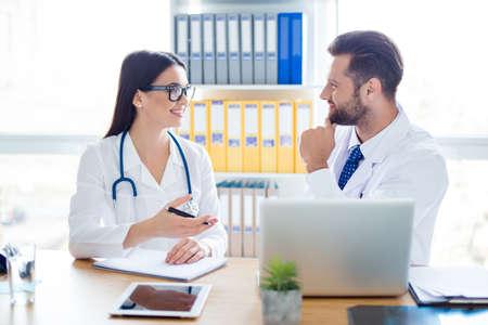 Due stagisti in uniforme bianca stanno discutendo la cura di un paziente. Sono felici per il suo recupero. Il posto di lavoro di doc è così moderno e leggero