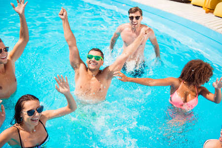 Chilling international youth is doing aquaaerobics, enjoying on tourists resort, beach pool sunny disco in the water, in diverse trendy bikinies, spectacles, celebrating holiday dance motion