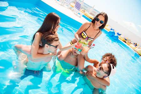 Gelukkige drie koppels roosteren met drankjes in het zwembad, jongens piggy back hun dames, zon, plezier, vakantiemodus, luxe zwemmen en oog slijtage, toeristenoord. Stockfoto