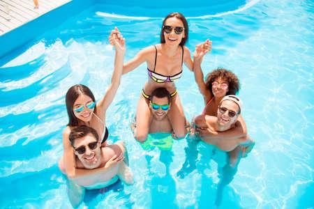 Hoge hoek shot van drie gelukkige vriendjes meeliften hun vriendinnen in het resort, in het zwembad, transparant helder water, vrolijke glimlach