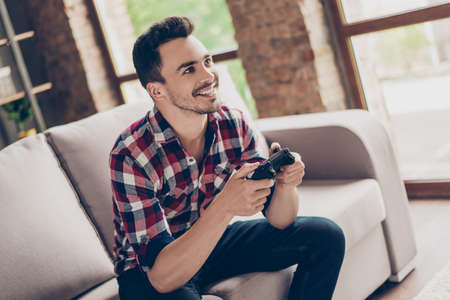 Portrait of attractive brunet hipster with bristle, holding joy stick and playing videogames on tv at vacation, sits at home on the cozy couch, successful, he is winning at crazy car race Stock Photo