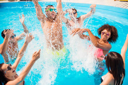 Tourists are enjoying at the pool sunny beach disco, splashes of water.