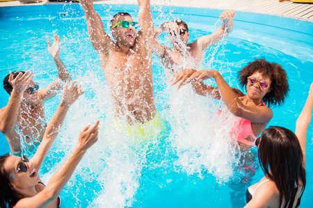 Toeristen genieten bij het zwembad van de zonnige stranddisco, spatten van water. Stockfoto