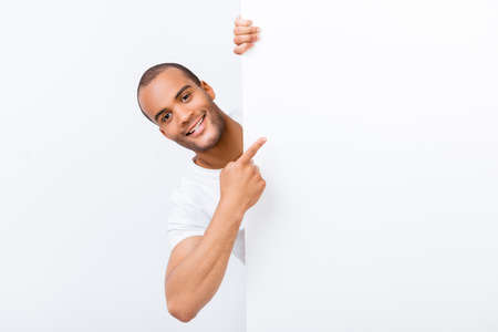 Happy amazed young mulatto guy is popping out from white blank banner, pointing at it with finger, wearing white t shirt, on white background Foto de archivo