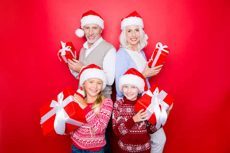 granny and grandad: Four relatives - excited siblings and married elder couple of grandad and granny with presents, in knitted cute traditional x mas costumes, isolated on the red background, enjoy, beaming smiles