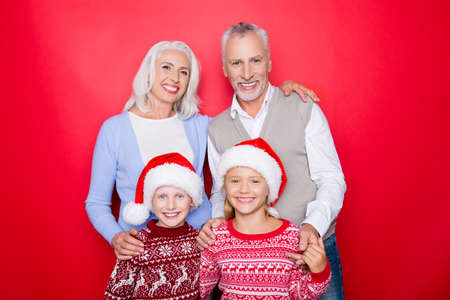 Four caucasian relatives bonding isolated on the red background, married elder couple of grandad and granny, grey white hair, excited siblings, in knitted cute traditional x mas costumes, togetherness Stock Photo