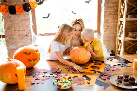 Mommy and two siblings made a jackolantern, peeking inside it, desktop with yellow candles, treats, fall leaves, little black bats on windows, garlands Banco de Imagens