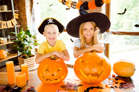 Close up cropped photo portrait of two small charming kids at halloween party indoors - blond small fairy and pirate, bonding, on top of hand cutted pumpkins, cheerful toothy smiles, indoors at home Stock Photo