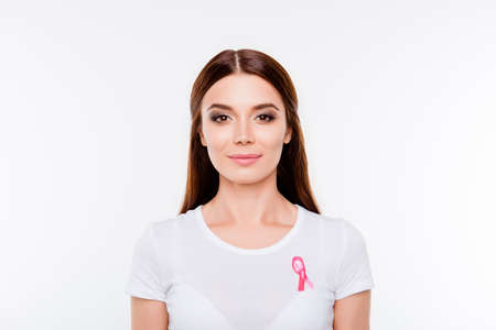 Health care, women and medicine concept. Portrait of smiling young lady in white t shirt with pink breast cancer awareness ribbon on her breast, isolated on white background