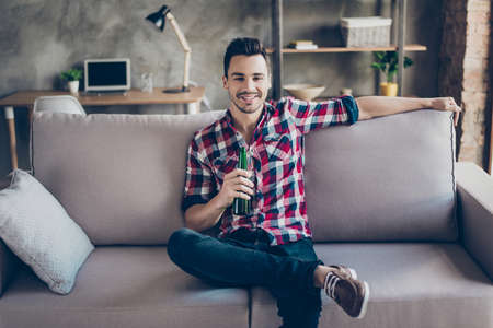 Young brunet hipster with bottle of beer at home, sitting on couch in casual smart, trendy fashionable shoes.