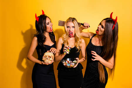 Terrifying gothic ladies with beaming white canines, cruel eyes, holding knife, gummy worms, braincase Stock Photo