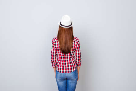 Back view snap model shot of young brunette woman in casual outfit and hat, standing on pure light grey background