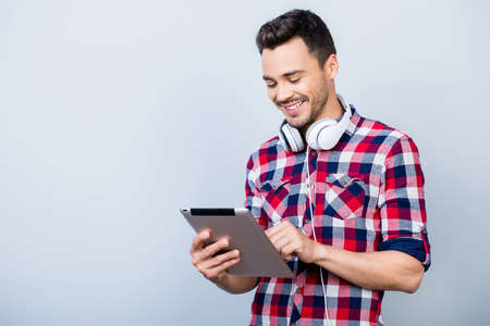 Successful young brunet freelancer hipster in checkered shirt is standing on the pure grey background with tablet, smiling, looking at it Фото со стока