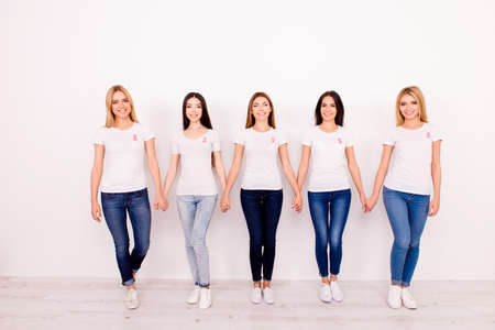 Life after fighting breast cancer exist. Carefree, international, cured, cheerful five girls are holding each other`s arms, walking to new life together, with pink ribbons symbols on chest