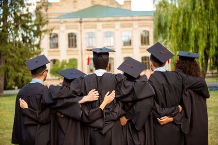 Back view of six successful graduates in black robes, bonding, in mortar-boards with red tassels, black gowns. They did it, passed exams, finished course of studies, got the master degree together Reklamní fotografie