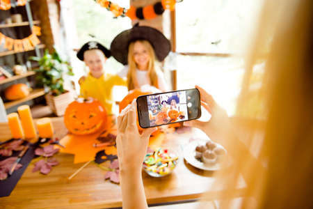 mommy is photographing her kids. Not clear shot of dressed in halloween headwear kids, bonding, mum is taking photo on her telephone, halloween decorations, focus of cell