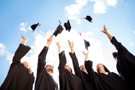 공기에서 그들의 모자를 던지고 축 하, 웃음, 즐기는 검은 가운 6 명의 젊은 multiethnic 졸업생의 쾌활 한 그룹의 낮은 각도 쐈 어. 스톡 콘텐츠