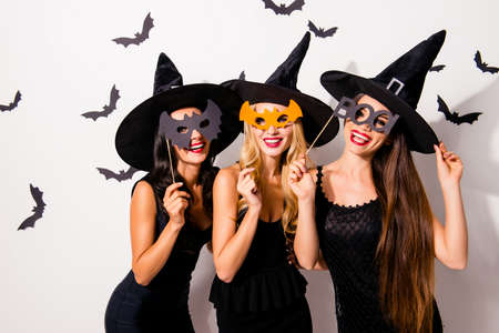 Group of three diverse charming coquettes in dark masquerade elegant dresses, masks on eyes, smiling, enjoying near decorated wall with bats, toothy beaming smiles, scary bright cosmetics hot figures Фото со стока