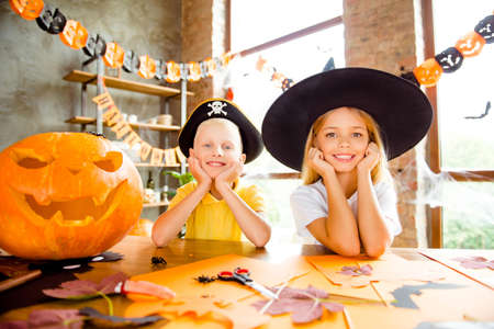 Close up cropped photo portrait of two small kids at halloween party - blond small witch and pirate, bonding, holding heads with arms, cheerful toothy smiles, indoors at home, loft style decorated