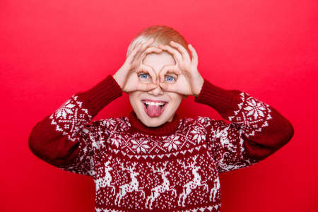 Small caucasian kid enjoying making a funny face, sticking out his tongue, playing with his hands for fun, in traditional x mas knitted clothing, isolated on red background