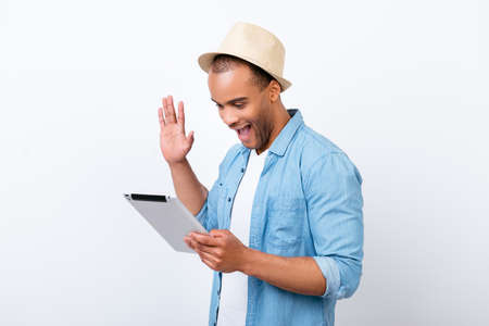 oung cheerful afro american guy is waving in camera while having video call from holiday, isolated on white background, in hat, with wide open mouth