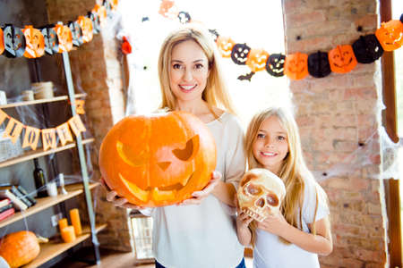 Adorable small blonde girl and her mommy are showing decorations for a halloween party, pretty mum is with big carved pumpkin, in room with garlands, bats and spider nets on the window