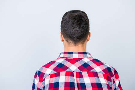 Rear view photo of young brunet hipster with modern haircut, in a checkered shirt, standing isolated on gray background
