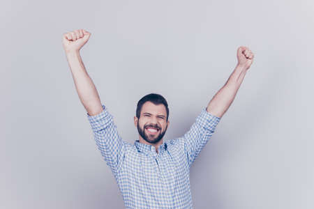 Yes! Wow! Happy young student passed all exams, he is celebrating, wearing smart shirt, jumps on a pure light background