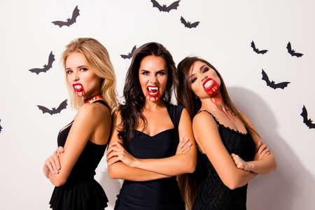 ¡Truco o trato! Pesadilla aterradora. Grupo de tres vampiros enojados sedientos calientes con sangrientas bocas, labios rojos, de pie con las manos cruzadas en el vestido oscuro, agresivo, molesto y dispuesto a matar Foto de archivo
