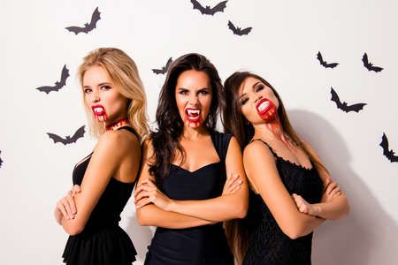 Trick or treat! Terrifyng nightmare. Group of three hot thirsty angry vamps with bloody mouthes, red lips, standing with crossed hands in dark dress, agressive, annoyed and willing t kill