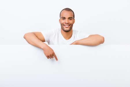 陽気な若いアフリカ人は白の空白のバナーの後ろに立って、カジュアルな服装で、白い copyspace で下向き