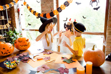 londe mommy with two little dressed sister and brother, creepy costumes, eyewear and head wear, scaring each other in decorated nice loft light room indoors at home near the windows