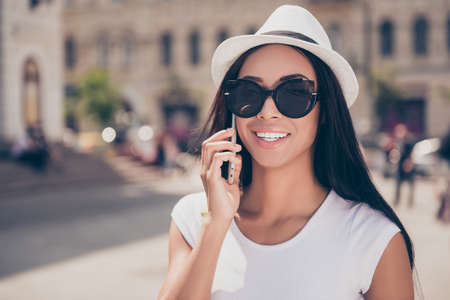 Attractive stylish mixed-race lady with bronze skin and trendy eyewear is speaking on her digital pda on holiday while having a strool outside in a sunny town, enjoying the quality of call