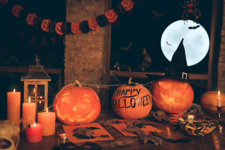 Creepy attributes of halloween feast hand cutted pumpkin with devil smile and eyes in witch hat, candles, fall leaves, treats, spider webs, net, skull, all prepared on wooden desk top, white full moon Stock Photo - 86628423