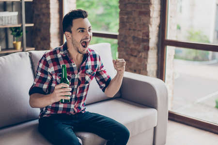 Brunet hipster freelancer with bristle in casual smart is excited watching the game at holiday, having drink, sitting on couch, joyful grimace, gesturing victory with fists of hands