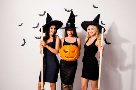 Group of three flirty coquettes in masquerade elegant dresses, red lips, handmade cutted decorative jack-o-lantern, in dark headwear, on white wall`s background with scary small creatures vampires Фото со стока