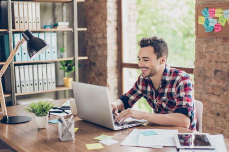 Cheerful young brunet freelancer is smiling, typing on his laptop in nice modern work station at home, in casual smart wear