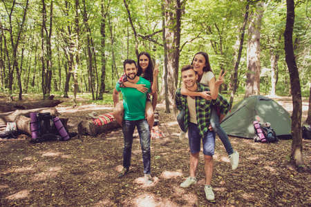 Camp in the sunny wood, tent and backpacks. Two lovely couples, guys are piggybacking their girlfriends, happy, smiling