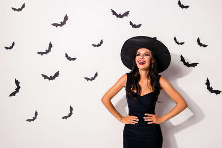 Hot flirty cheerful brunette slim lady magician is laughing, in dark dress, with arms on waist, in cap, with bright red lips, white wall background with black bats on it, charming and elegant
