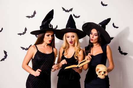 Three hot sorceress supersition spiritualists, practising occultism, with skeleton head, diabolic, satanic, devil, hex, wiccan exorcist paranormal ritual, dark spirits culture, astonished grimaces Imagens