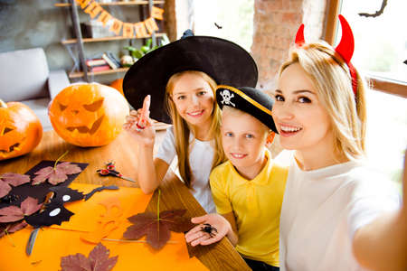 Family portrait of three at halloween party. Happy mom and her cheerful kids - blond small witch and pirate, bonding, lady is making selfie, siblings holding creepy decorations in arm palms Stock Photo