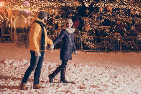oung couple in love is walking in a park of attractions outdoors at the eve, enjoying, holding hands, dressed warm, looking at each other, huge christmas tree behind